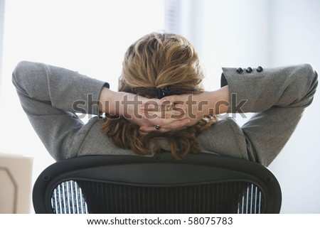 A businesswoman is seated in an office chair with her hands behind he head.  She is looking away from the camera.  Horizontal shot. - stock photo