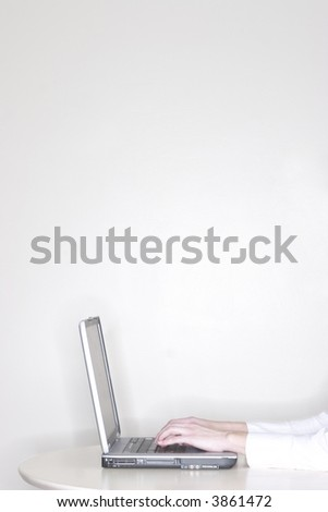 a businesswoman is sitting at her desk using her laptop and working with a close-up of her hands on the laptop - stock photo
