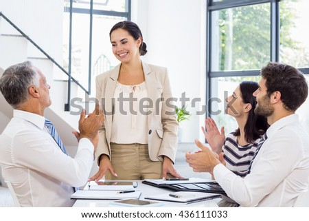 A businesswoman is standing in front of her colleagues who are applauding at work - stock photo