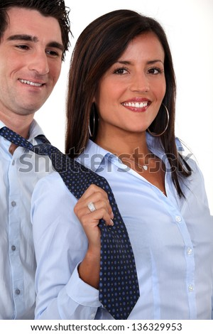 A businesswoman pulling her colleague by the tie. - stock photo