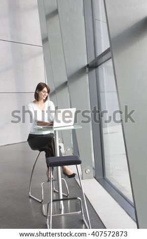 A businesswoman sitting in modern office building using a laptop - stock photo