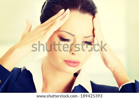 A businesswoman with a headache holding head - stock photo