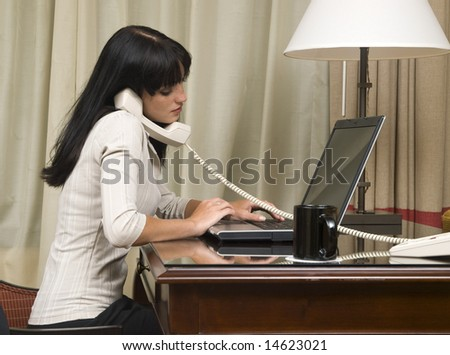 A businesswoman works on her laptop in her hotel room during a business trip. - stock photo