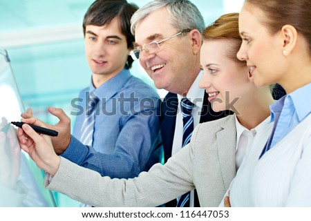 A businesswoman writing on whiteboard with a highlighter while explaining something to colleagues - stock photo