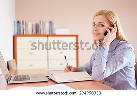 A businesswoman writing something in her diary while sitting in her office - stock photo