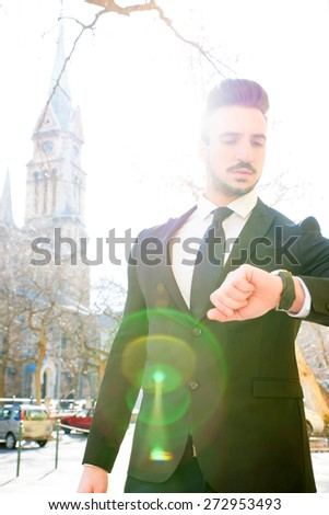 A busy business man checking the time on a early afternoon in a european city.  - stock photo