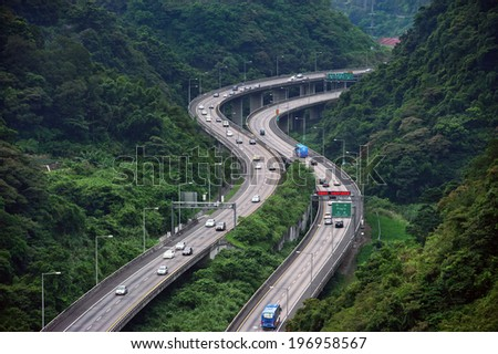 A busy road curving and going further into the mountains. - stock photo