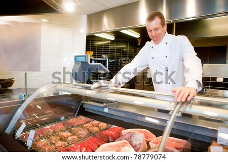 A butcher at a fresh meat counter in a grocery store - stock photo