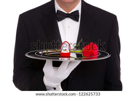 A butler holding a silver tray upon which is a diamond engagement ring in a heart shaped jewelry box and a single red rose, on a white background. - stock photo