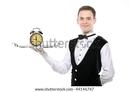 A butler holding a silver tray with a alarm clock on it - stock photo