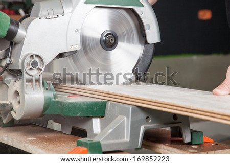 A buzz saw is sawing two pieces of laminate at the same time. - stock photo