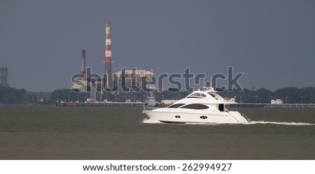 A cabin cruiser boat headed out to the Chesapeake Bay by way of the York River in Virginia during an approaching thunderstorm on a warm humid summer day - stock photo