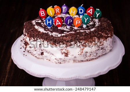 A cake and it's candles that read happy birthday. - stock photo