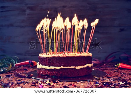 a cake topped with some lit candles before blowing out the cake, on a rustic wooden table full of confetti, party horns and streamers, with a filtered effect - stock photo