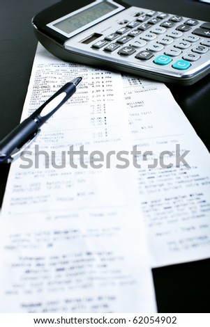 A calculator, a pen, bills, receipts on the black table - stock photo