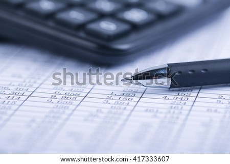 A calculator and a ball pen is on a balance sheet. Concept for sales, profit and cost. - stock photo