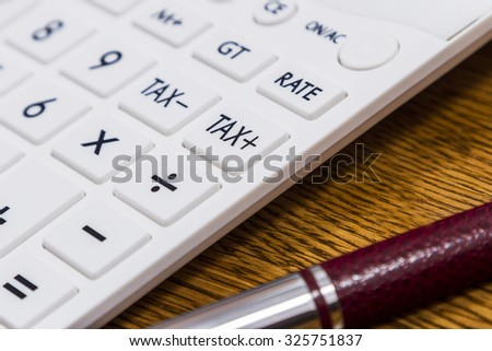 A calculator and a pen on desk for calculating taxes - stock photo