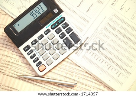 A calculator and pen on top of financial newspapers. - stock photo