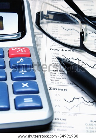 A calculator, ball-pen and glasses on top of a stockmarket report - stock photo