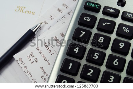 A calculator with receipt and menu - stock photo