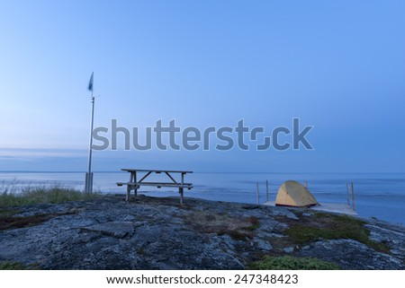A calm and nice camping platform with a yellow tent on a rocky outpost near the sea on a summer evening. - stock photo