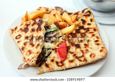 A calzone-style covered pita pie, containing chicken souvlaki meat, salad and cheese, served with french fried potato chips - stock photo