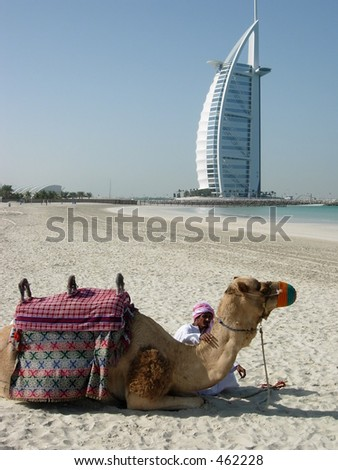 A Camel and an Arab posing in front of a luxurious hotel in dubai - stock photo