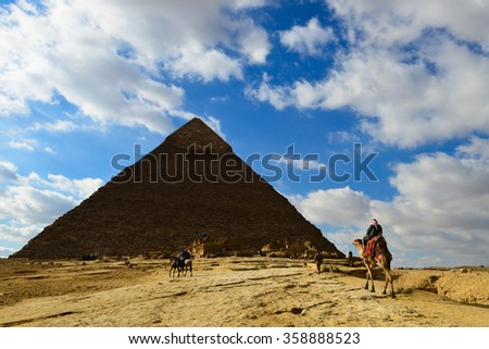 A Camel rider travels toward the Great Pyramid of Giza (Khufu) - Cairo, Egypt - stock photo