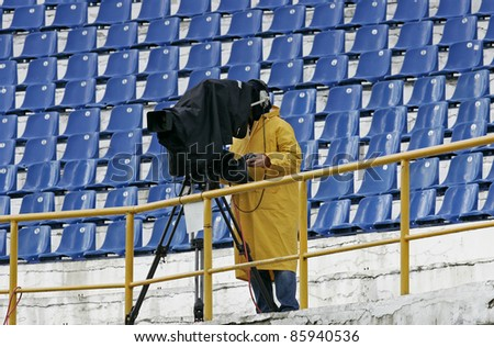 a cameraman filming a football game on a stadium in the rain - stock photo