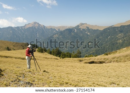 A cameraman standed and shot in the outdoor. - stock photo