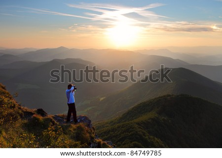 A cameraman standing and shoting in the outdoors - stock photo
