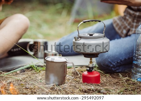 A camping tea kettle on a propane stove next to a metal cup - stock photo
