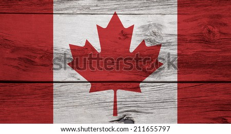 A Canadian flag on a rustic wooden background. - stock photo