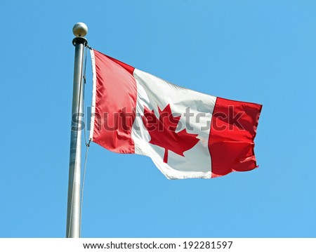 A Canadian flag waving in the wind against a blue sky - stock photo