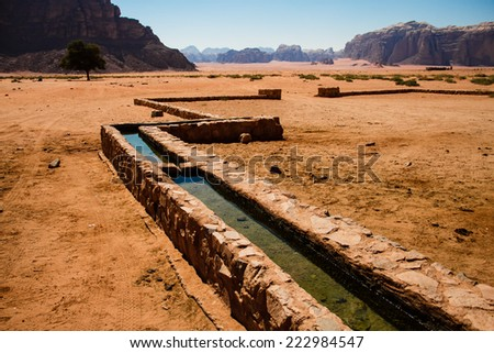 A canal brings water down the mountain in Wadi Rum to Bedouins livestock. - stock photo