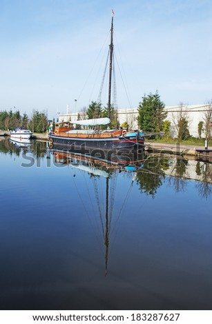 A canal view with barges and water craft moored to the bank - stock photo