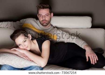 A candid photo of a young couple watching TV - no cheesy un-natural smiles - stock photo