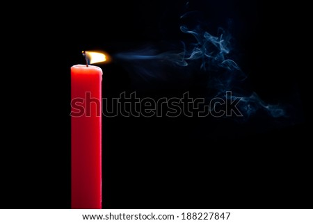A candle flame flickers as it's blown out by wind. - stock photo