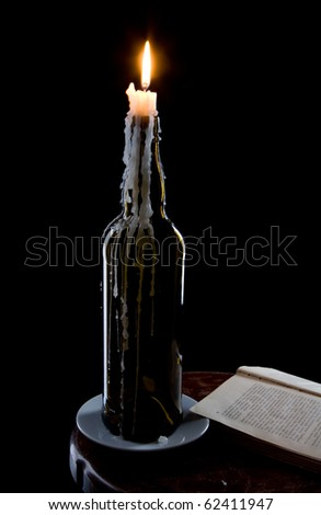 A candle in a bottle and a book on black - stock photo