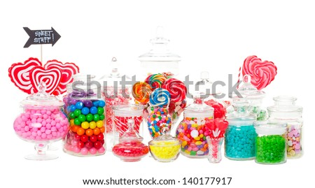 A candy buffet with a wide variety of candies in apothecary jars.  Shot on white background. - stock photo