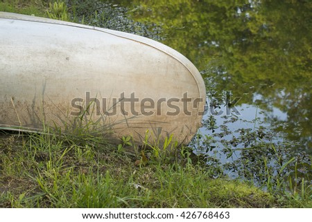 A canoe sits on the grassy shore of a pond.  - stock photo