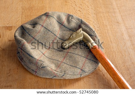 a cap and an walking-stick on a oak table - stock photo