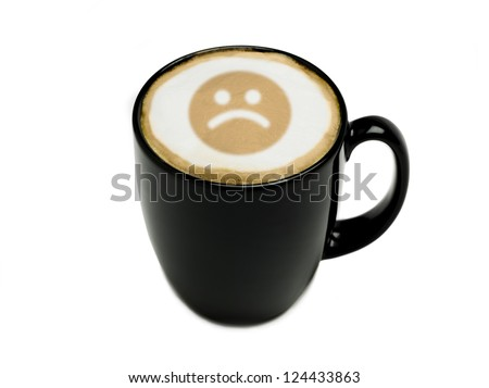 A cappuccino in a black mug with an unhappy face design made with coffee. - stock photo