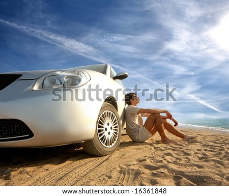 a car and a young man on the beach - stock photo