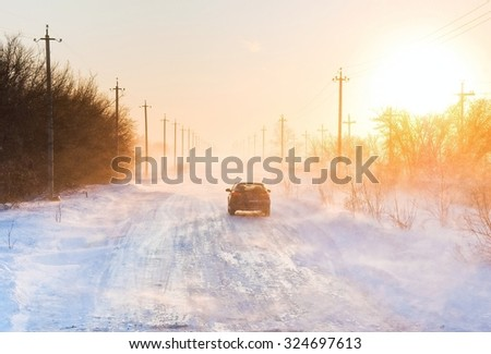 A car drifting on ice in a snowstorm in a frosty windy winter day - stock photo