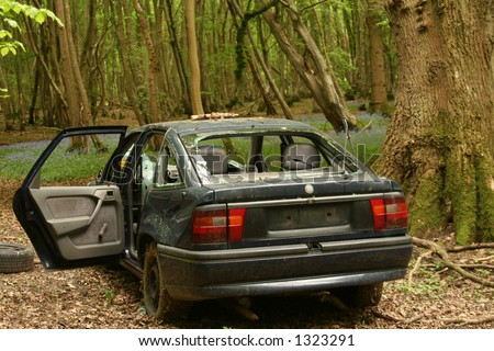 A car dumped in a beautiful woodland setting and wrecked, vandalised beyond use for no reason other than the mindless pleasure of the culprits thus destroying the area. - stock photo