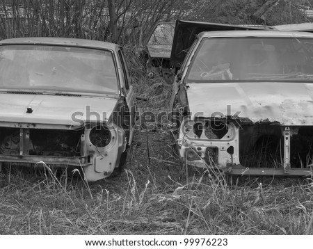 A car graveyard with old and rusted car wrecks in black and white - stock photo