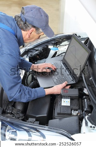 A Car Mechanics with diagnostic notebook on car - stock photo