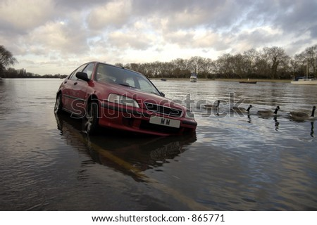 A car parked by the side of the road surrounded by water at high tide - faked plate - stock photo
