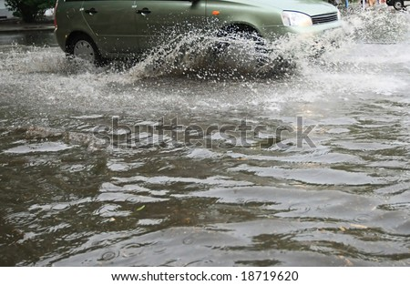 A car splashes through a large puddle on a wet road. - stock photo